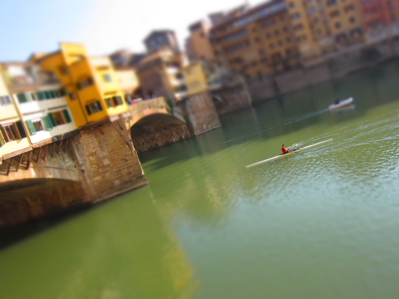 Rower passing under the beautiful Ponte Vecchio.